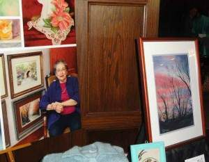 "Lorene Peterson with several of her paintings, including her prizewinning piece, ""Kansas Sunset,"" far right."