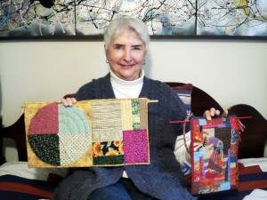 Resident Mary Burchill with two handstitched art projects.