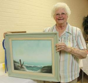 Resident Betty Piersol stands next to her artwork.