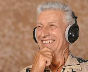A senior listening to music through headphones.