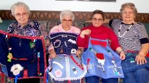 From L to R Eva Beeks, Della Catron, Wilda Buffo, and LaVona Morrison are each holding one of the lap/fidget quilts that they made. So far more than 10 lap/fidget quilts have been made.