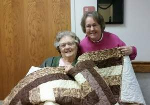 Louise Feldt and Nola Vice pose with one of Louise's many quilts.