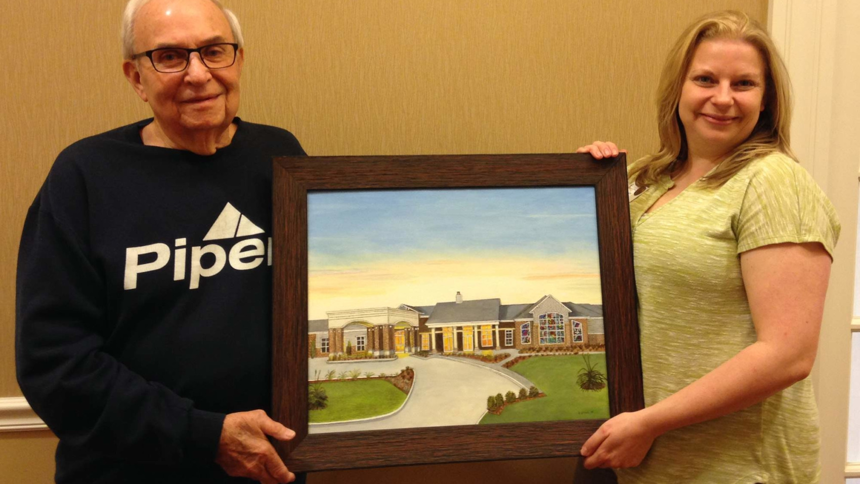 """Gary Stahl presents his panting, """"Our New Home"""" to Amy Watson, life enrichment director."""