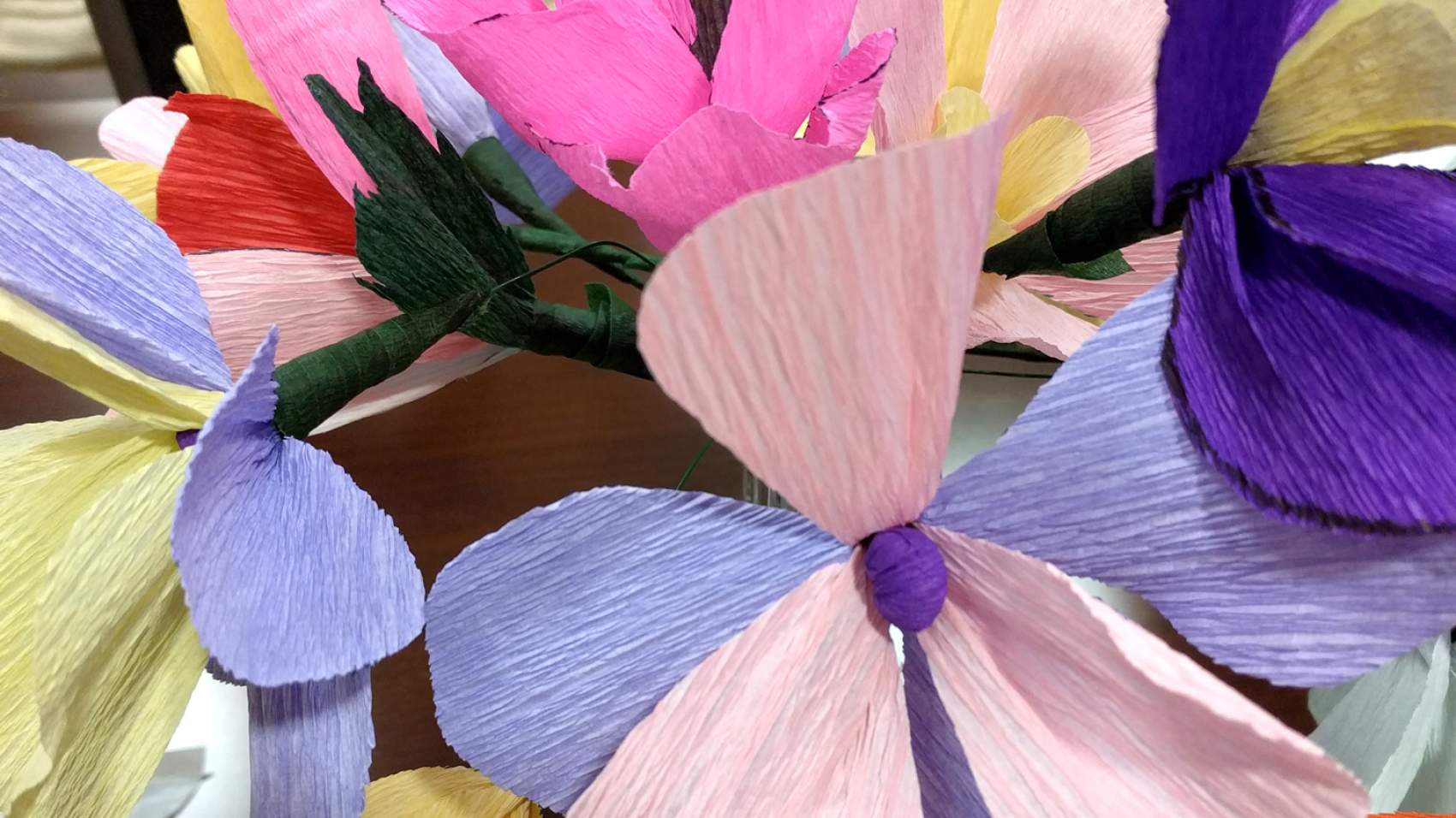 Residents at Valley Glen help create colorful paper flowers made with fancy crepe paper and other supplies.