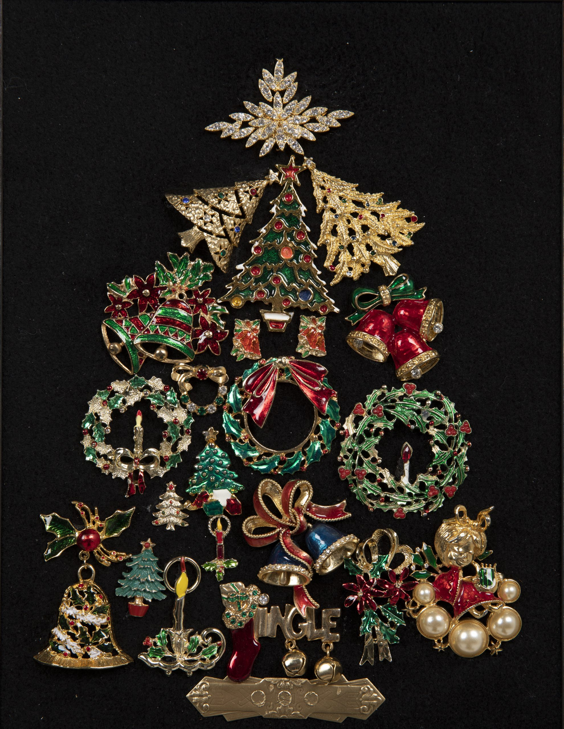 A Christmas tree created out of Christmas themed pins in a tree shape on a black background.