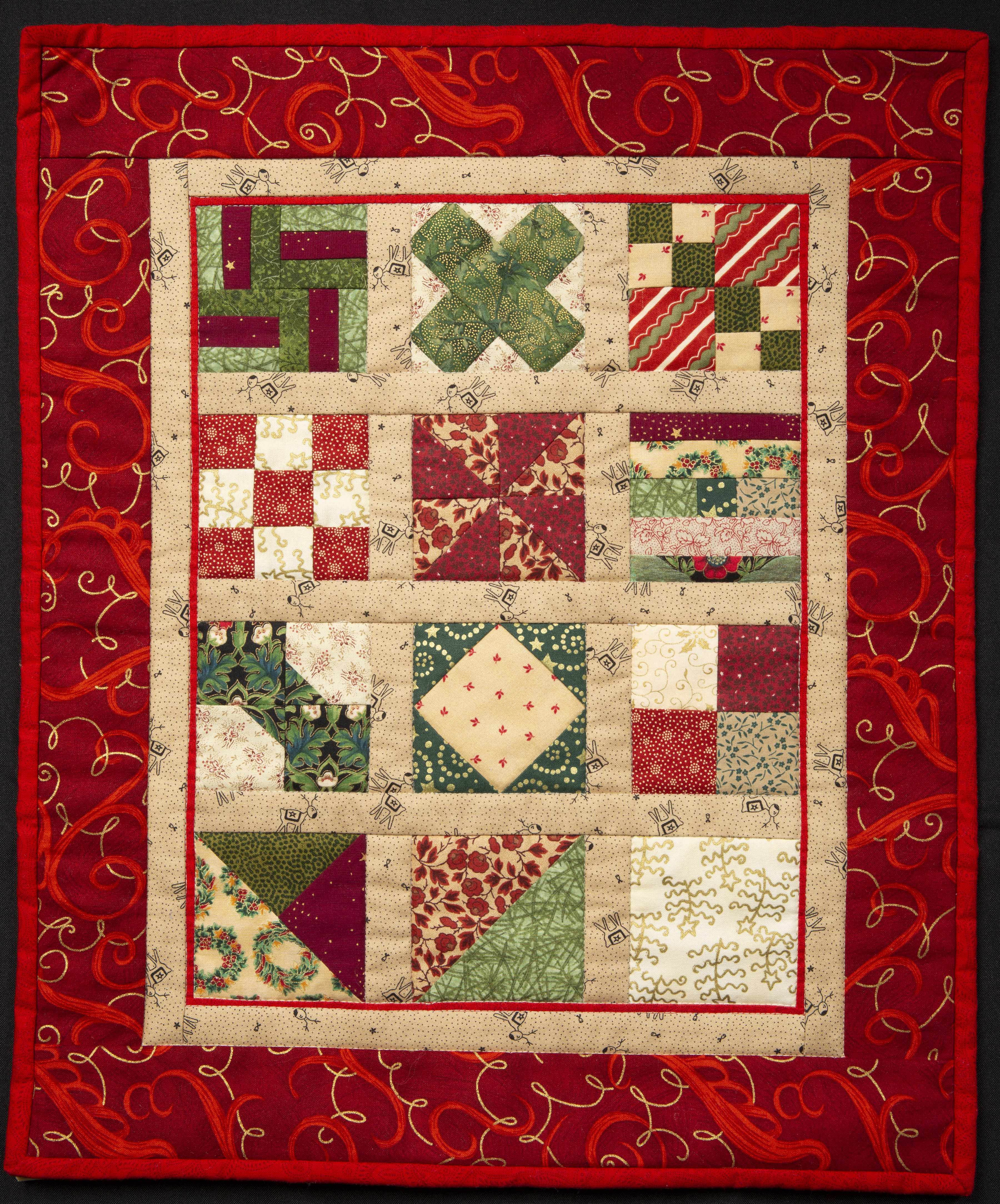 Twelve Days of Christmas - Quilt featuring festive red material used for the border with 12 blocks in the center made from several different patterned fabrics