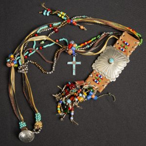 Fiber Arts - Bright Journey - necklace made of leather with colorful beads and silver concho with turquoise stone in center. Necklace has cross charm with turquoise and silver charm with indian head engraged on it.