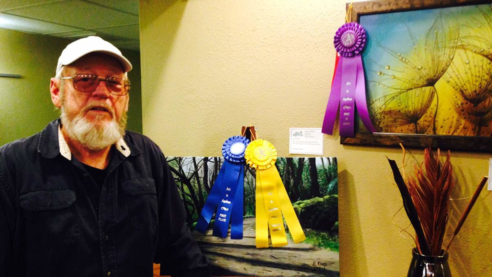 "John King poses with his pieces ""Walk in the Woods,"" which is People's Choice Professional, and ""Bubbles,"" which was Best in Show Professional."