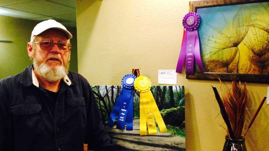 """John King poses with his pieces """"Walk in the Woods,"""" which is People's Choice Professional, and """"Bubbles,"""" which was Best in Show Professional."""