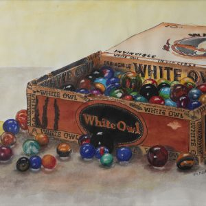 An old White Owl cigarrillo box filled with many colors of glass marbles in and around the box.