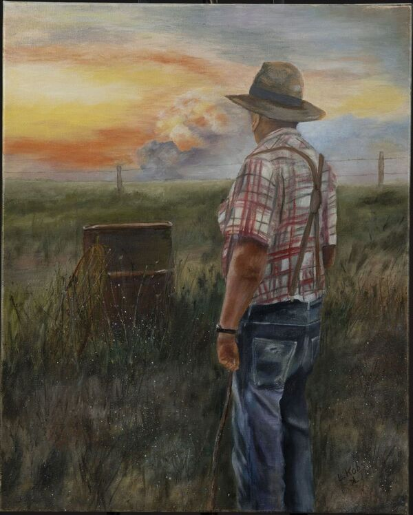 Man standing in a pasture looking off into the distance at a sunset behind clouds.