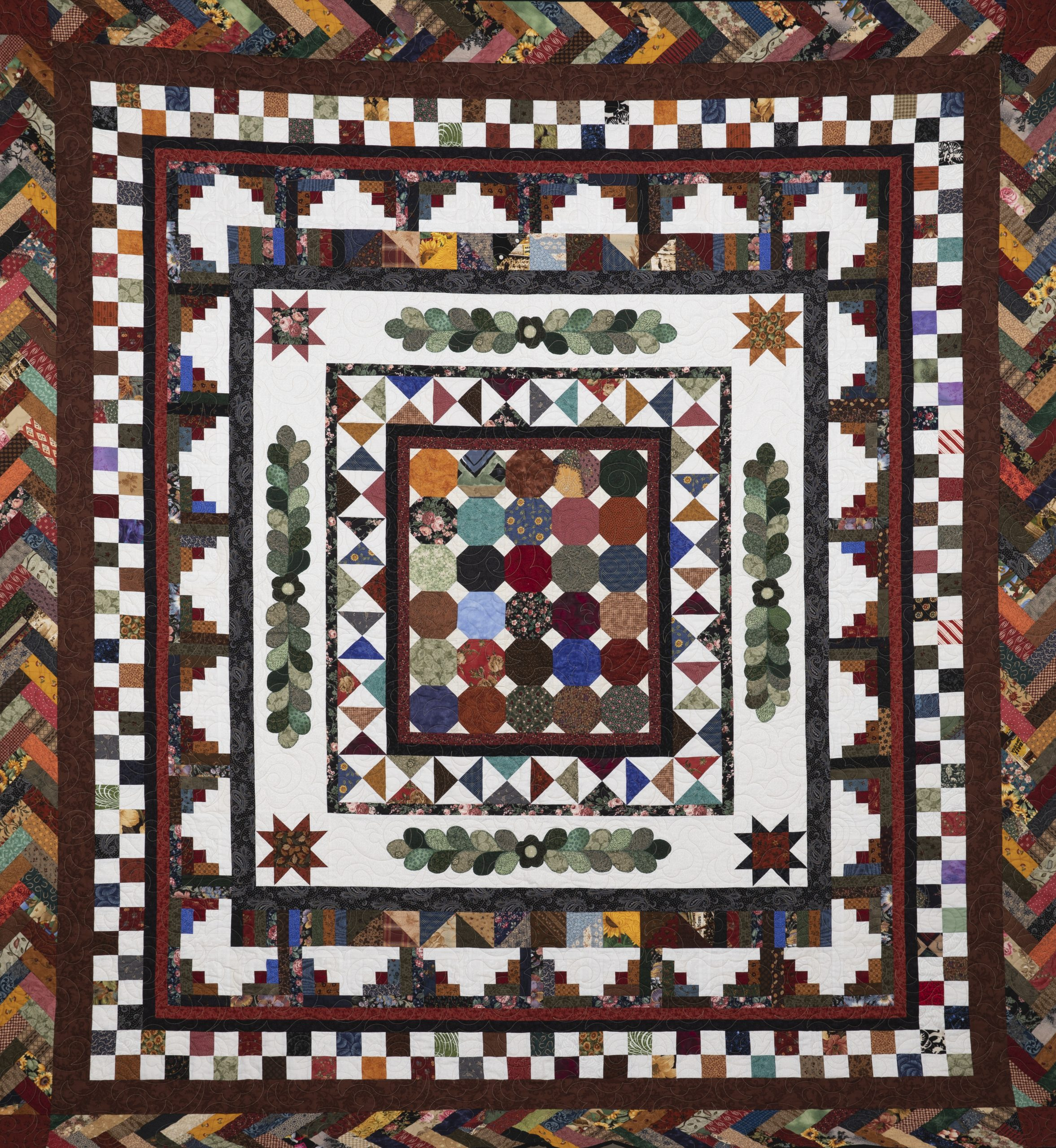 Quilt featuring fall colors and a chevron pattern around the edges giving the quilt movement around the edges
