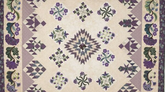 Quilt featuring purple flowers and purple and green shapes on an off-wite and lavendar background.