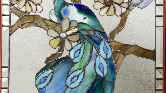 Sculpture 3D - Jasper the Peacock - image of a stained glass peacock in shades of blue on a brown branch with beige and blue flowers.