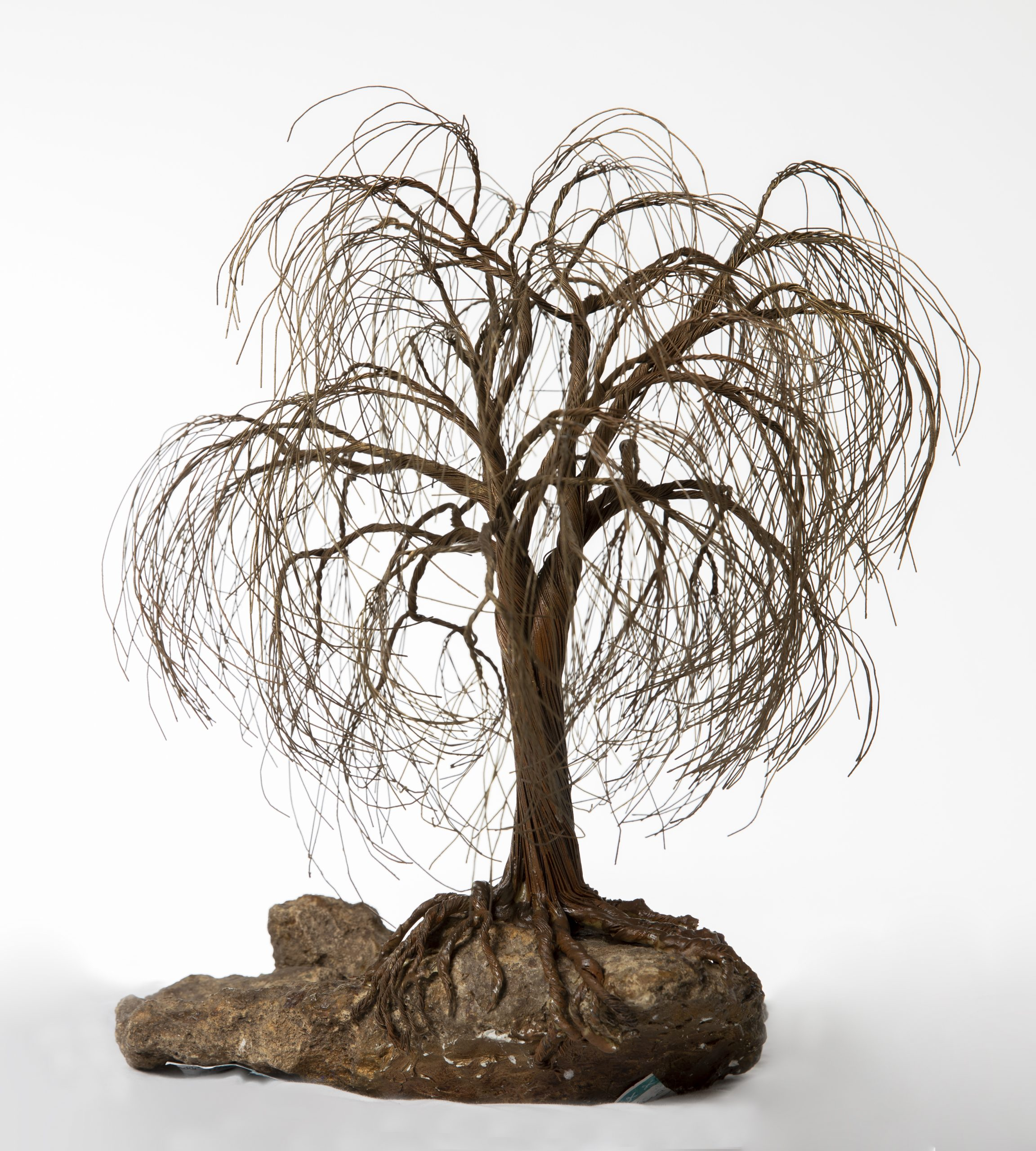 A sculpture of a willow tree hanging onto a rock made of a red-brown wire