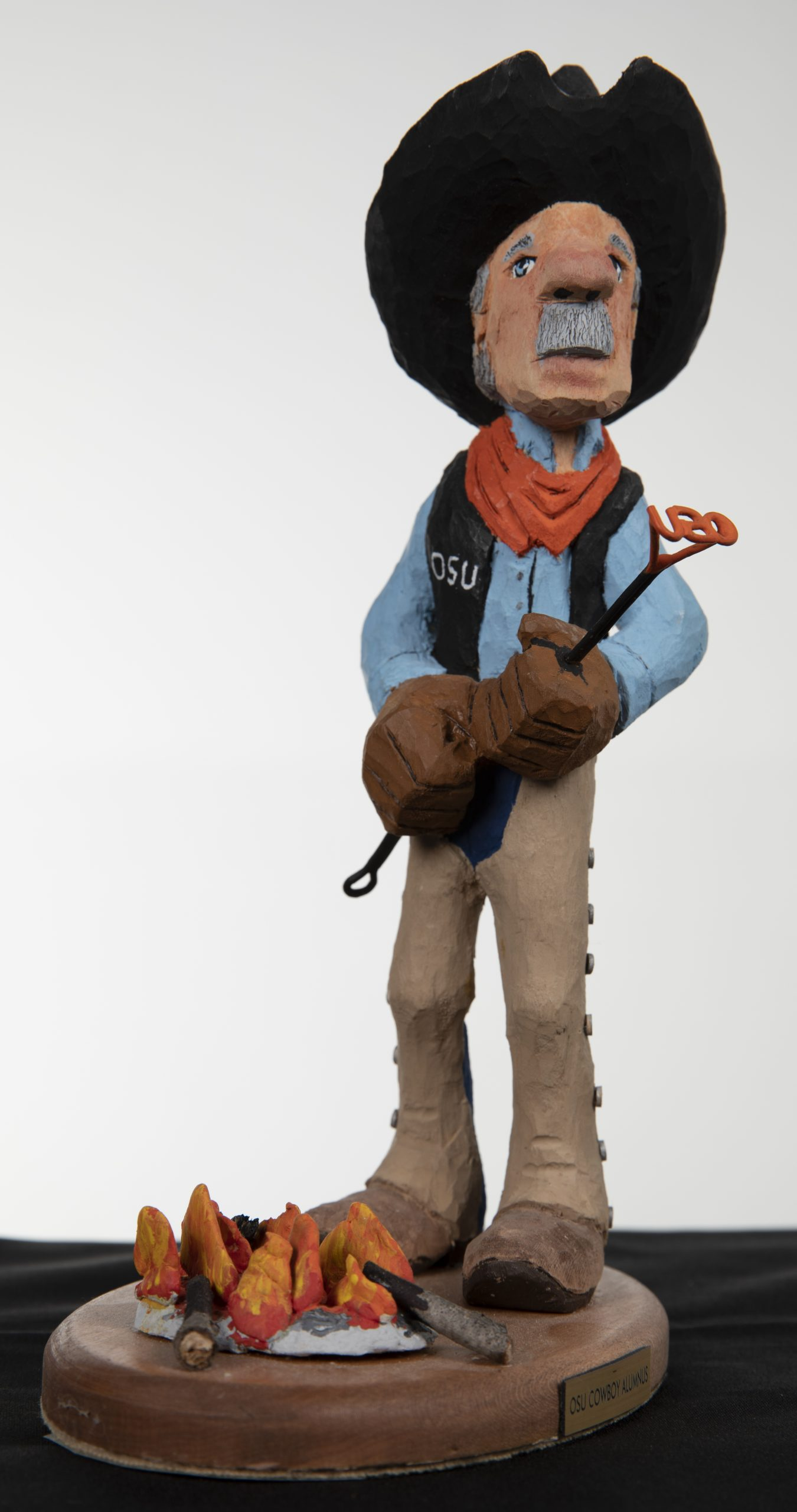 Scuplture of man dressed as cowboy standing over an open fire and holding a cattle brand