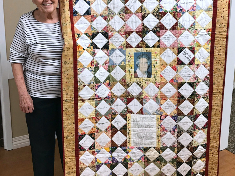 Leta Sherwood poses with the quilt she made to celebrate her mother's 100th birthday. The quilt included blocks of fabric signed by family, friends and even President G.W. Bush.