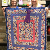 "Pat Powell with her daughter Sarah Griggs and Pat's quilt ""Magnusson Quartermania"" which won Best in Show and 1st place in Quilting"