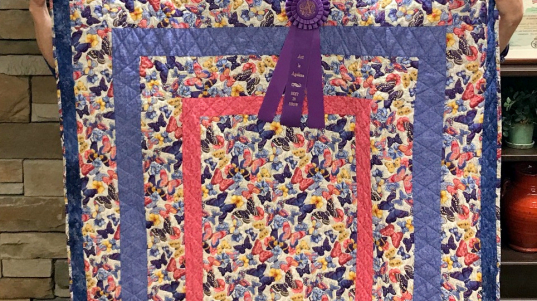 """Pat Powell with her daughter Sarah Griggs and Pat's quilt """"Magnusson Quartermania"""" which won Best in Show and 1st place in Quilting"""