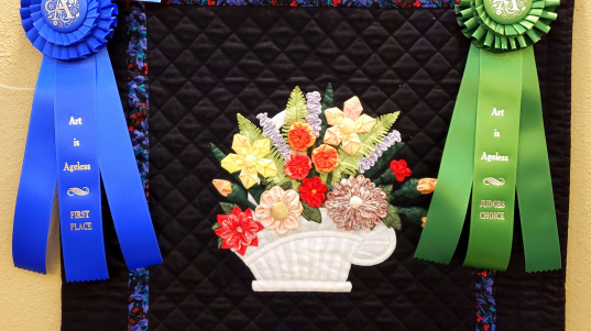 """""""Basket of Flowers"""" by Joan Butts wins Judge's Choice (amateur) and first place in Quilting: Hand-Stitched (amateur)."""